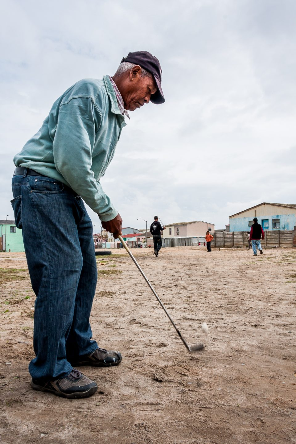 A man teaches a group of children how to play golf on the nearby community field.