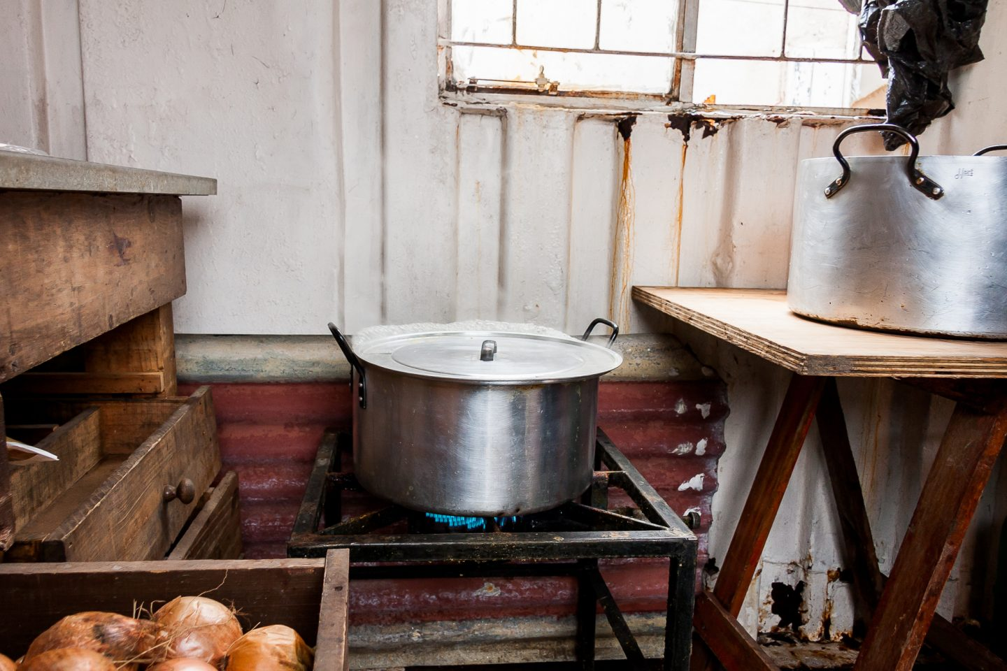 The big pot is on the stove in the container community center kitchen.