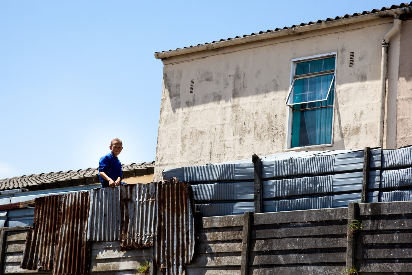 Looking onto the community field is a boy sitting on the fence of his family home.