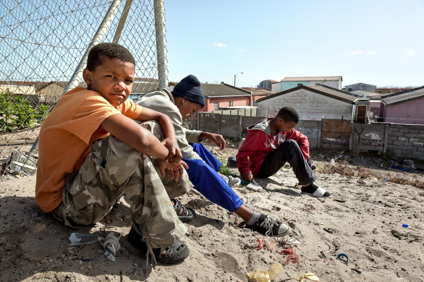 "A group of children ""hang"" out in the area across the community field. As activities for the youth are often sparse many children end up in situations of gangsterism, alcoholism and drug use."