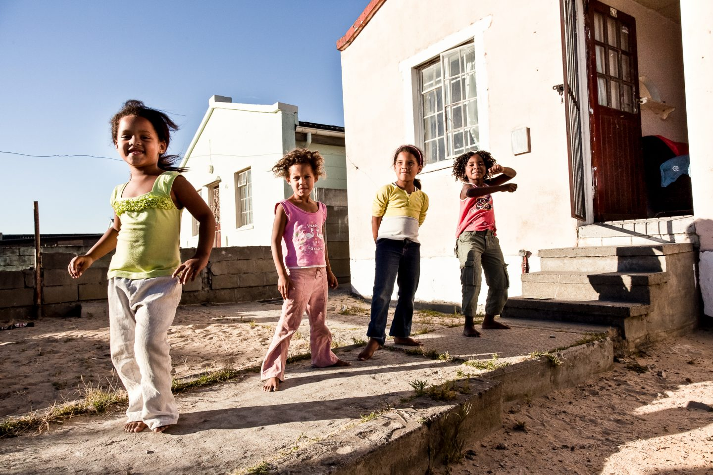 A group of girls are dancing outside the home of one of the street communities home.