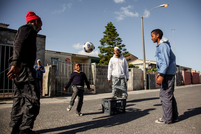 A group of youths playing soccer in the street of Theronsberg, Tafelsig.