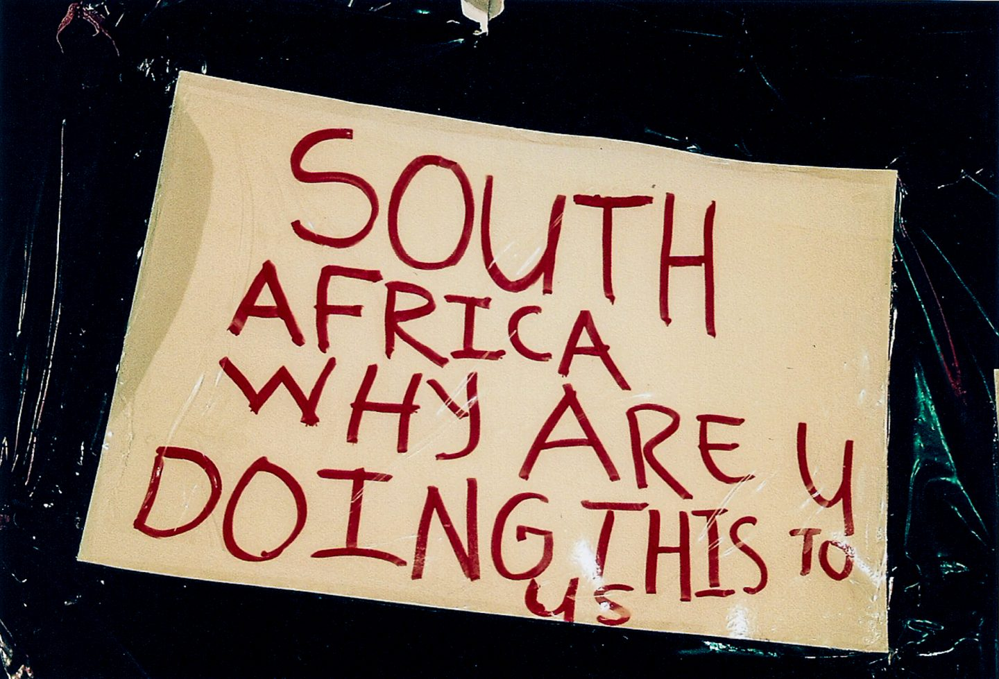 Sign made by victims of xenophobia and worried African expats outside the Cape Town central police station, 2018.