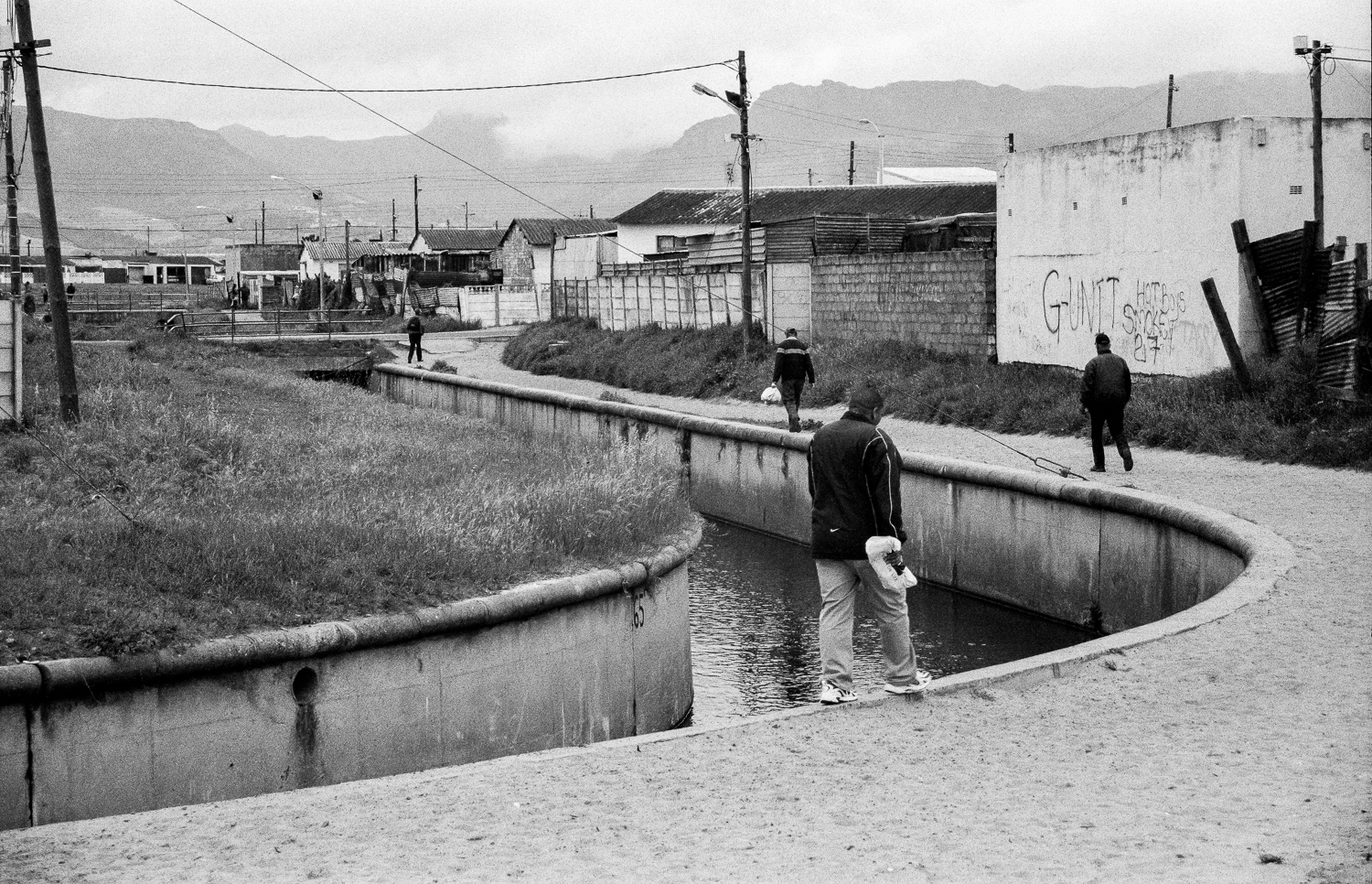 Men walking home after work, Steenberg in Cape Town, 2014.