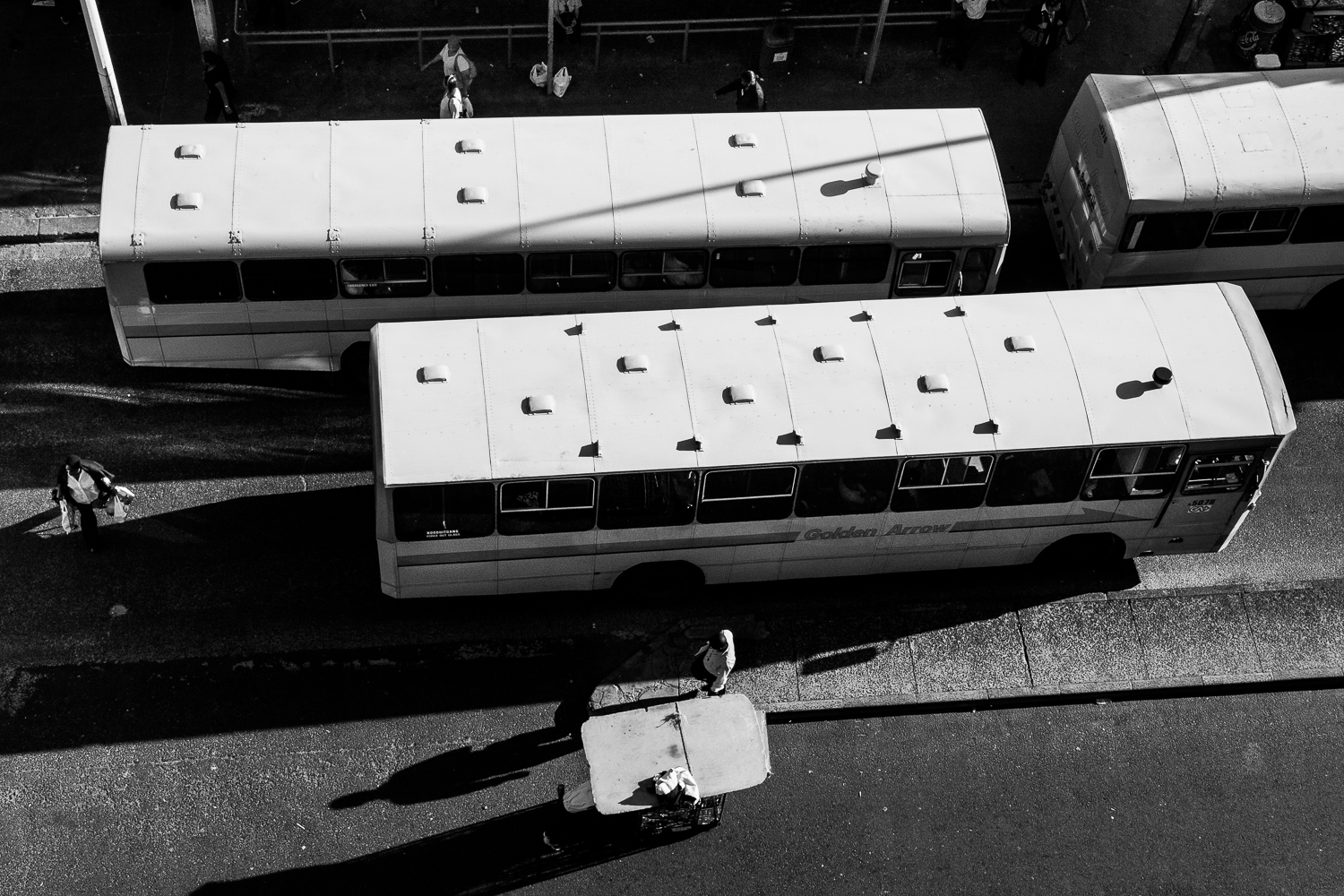 Busses leaving the central bus terminus, while stall owners are moving their temporary shop, Cape Town, 2009.