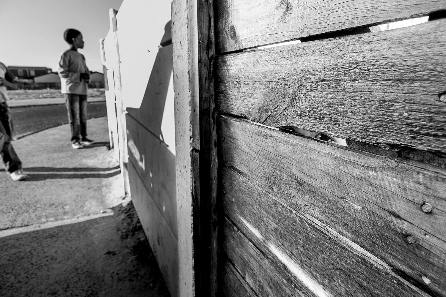 Child looking through the front gate of their home in Tafelsig, Mitchell's Plain, 2012.