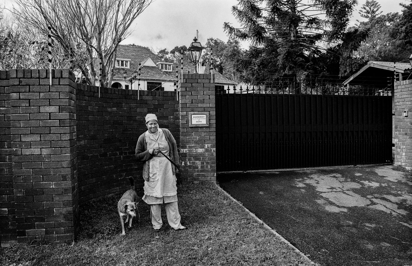 Domestic worker walking the dog outside employer's mansion, Bishop's Court, 2009.