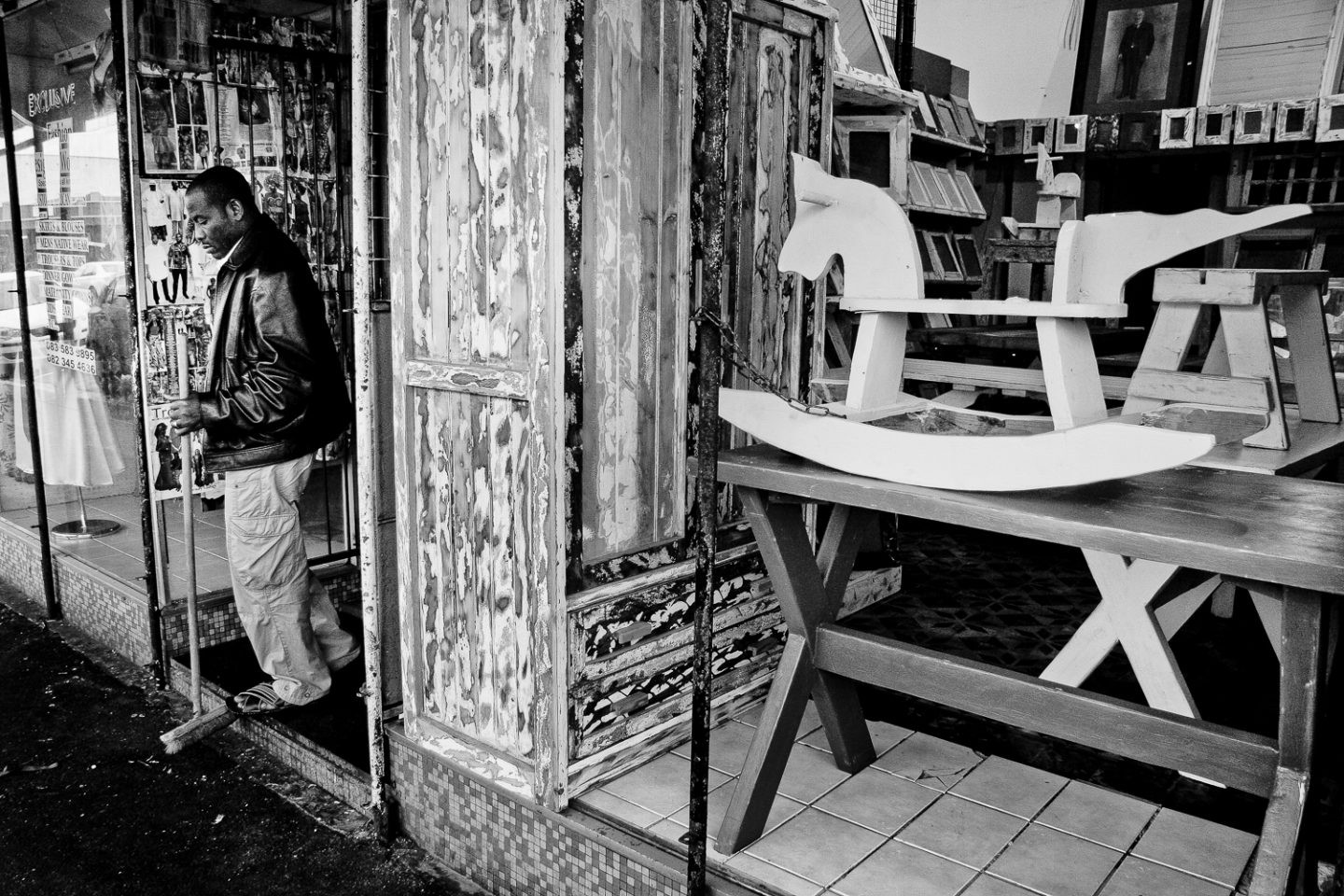 The owner of a woodworks store sweeps outside in the morning, Salt River 2011.